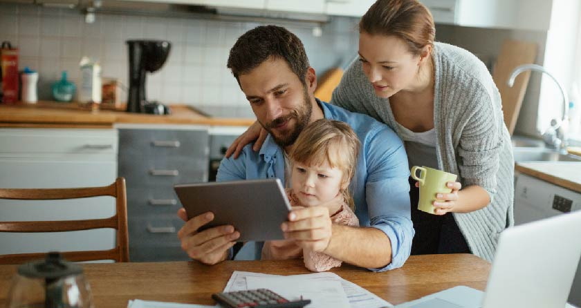 family with young child looking at tablet