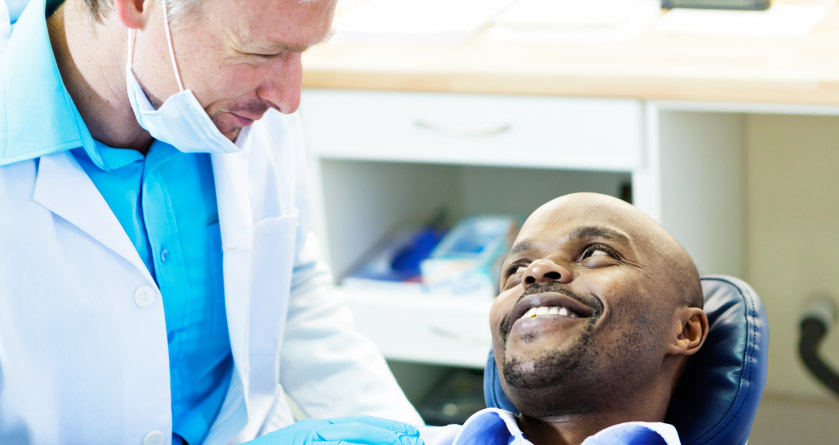 african american man in dental chair asking dentist about link between dental oral health