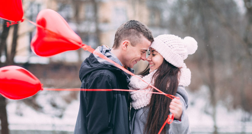 young man in black jacket and woman in winter hat and scarf standing outside in snow smiling at each other holding red heart balloons