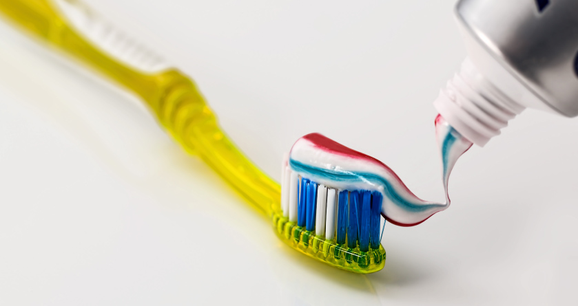 A yellow toothbrush with toothpaste being squeezed onto it