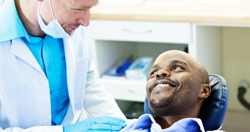 A male patient smiling at dentist after his root canal treatment