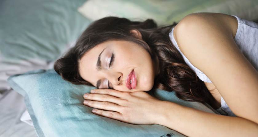 Close-up of a brunette woman peacefully sleeping on her side after limiting the effects of technology