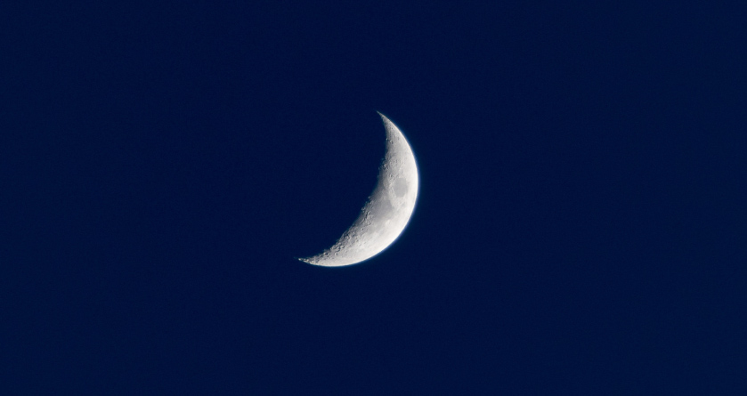 White crescent moon against a navy sky during the night, when most people sleep