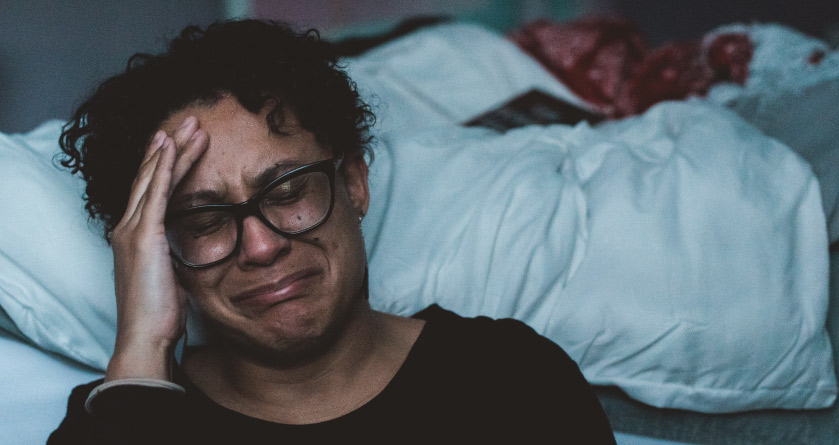 Closeup of a crying person with a headache due to sleep deprivation sitting on the floor next to their unmade bed