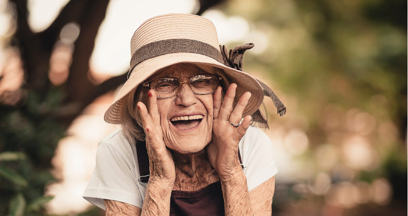elderly woman wearing a straw hat calling out with hands at the side of her face