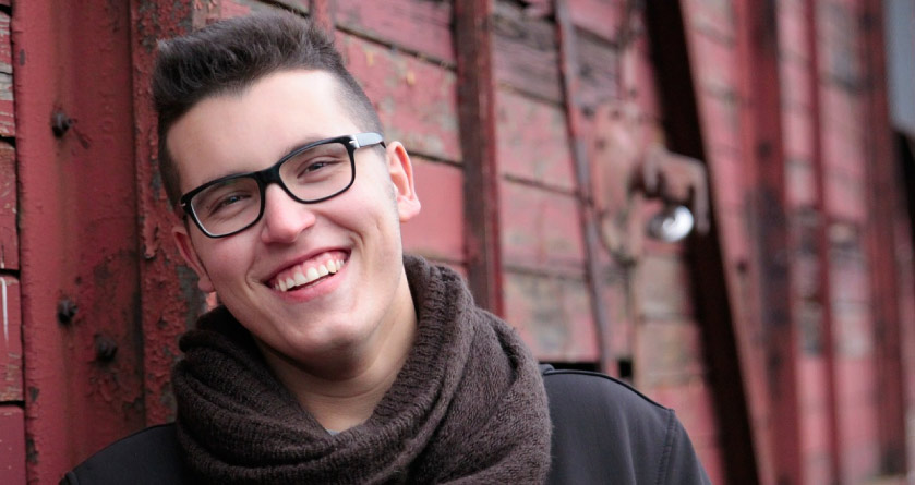 young man with glasses and a scarf smiling
