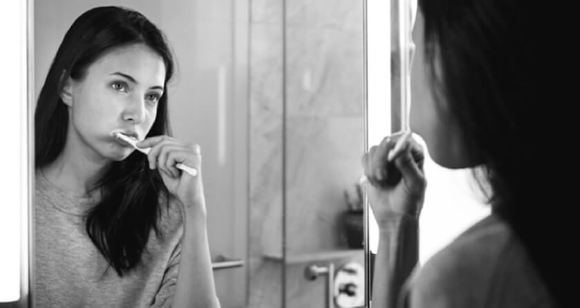 girl looking in the mirror brushing her teeth