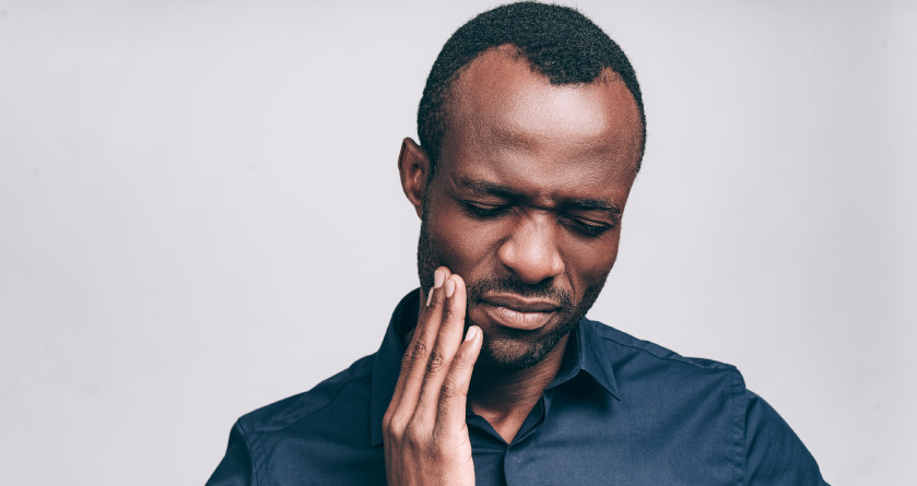 man holding his jaw with TMJ pain