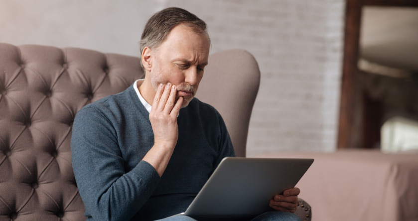 man looking at a laptop holding his jaw in pain from gum disease