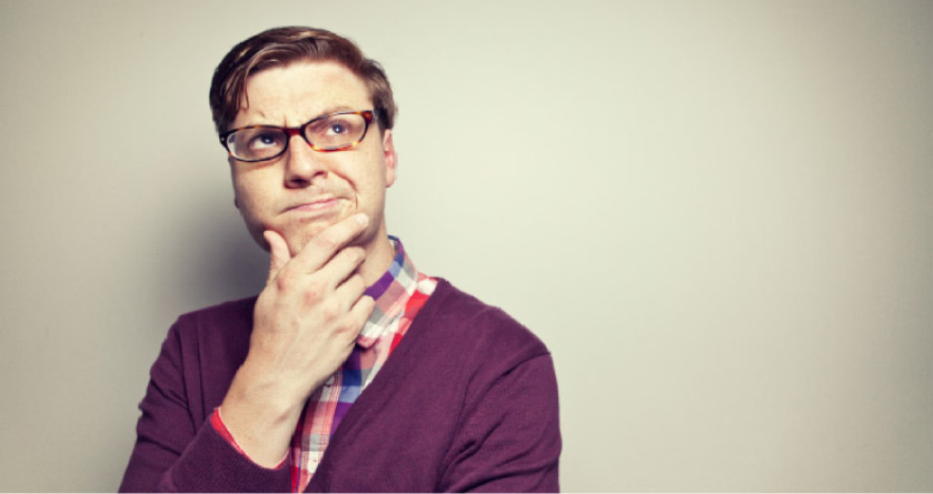 man wearing glasses and a purple sweater holds his chin pondering wisdom teeth removal