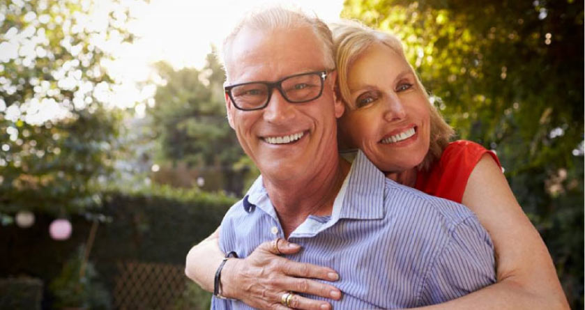 older couple hugging after learning about dental implant options