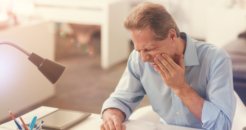 man sitting at a desk holding his jaw in pain from a failing dental implant