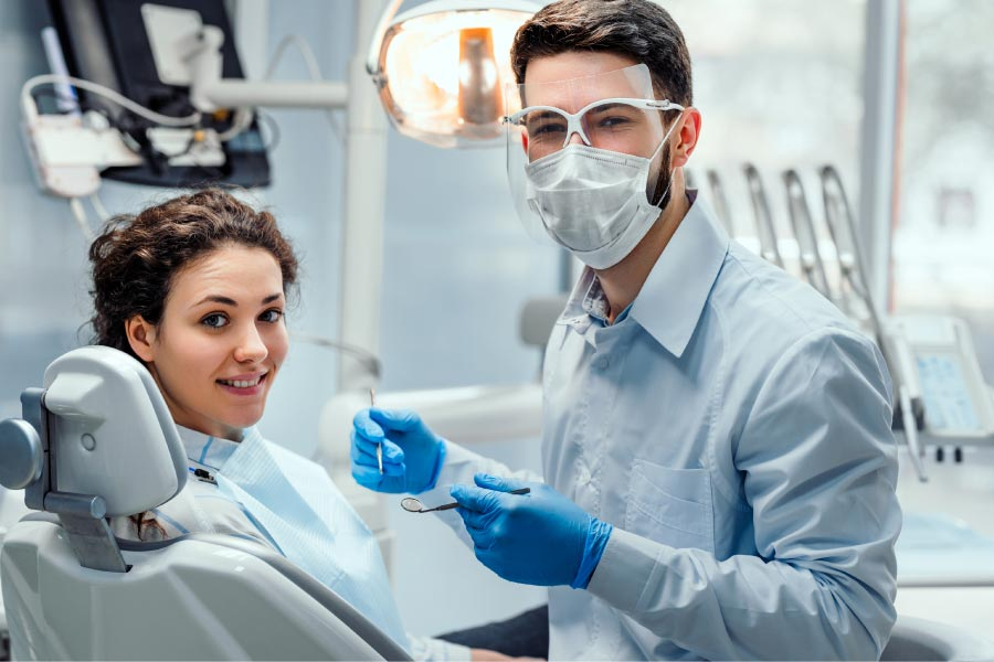 young patient sits in the dental chair as the dentist prepares for oral surgery while wearing a mask