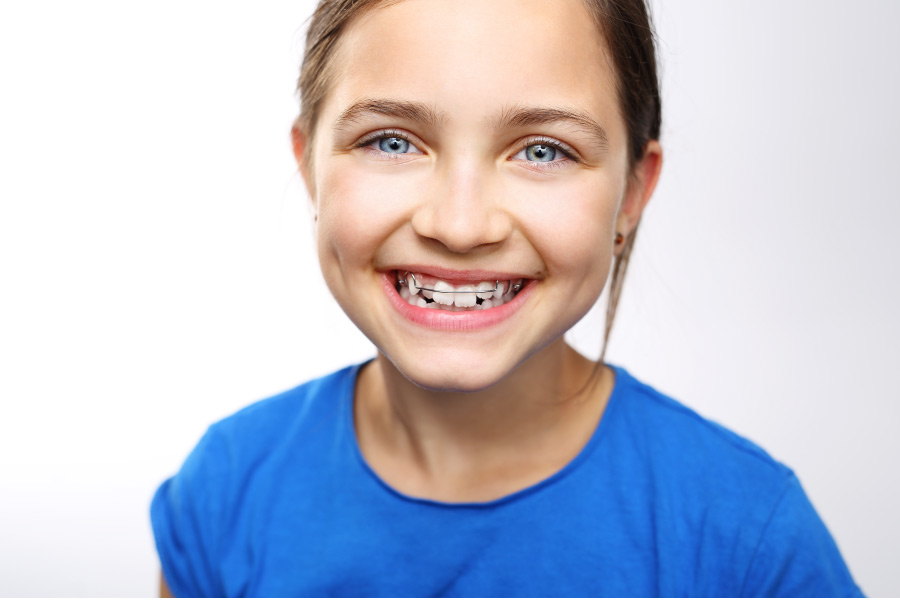 young girl smiles showing off her braces
