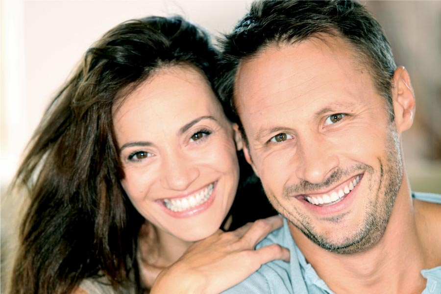 couple smile to show off their porcelain veneers