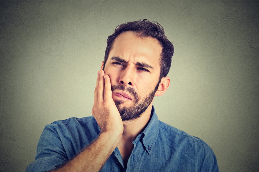 bearded man holds his jaw with painful gums